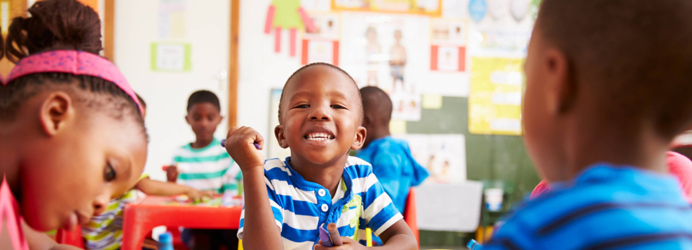 young boy smiling in summer class